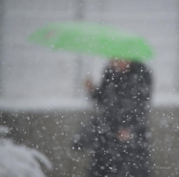 woman w green umbrella snowy day n